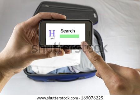 Businessman hotel booking with cellphone before close suitcase - stock photo