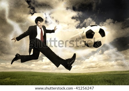 Businessman in a acrobatic pose kicking a ball in a stormy sky - stock photo