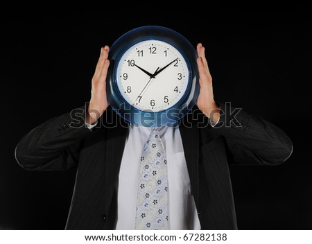 businessman in a black shirt holds clock in the face of on a black background