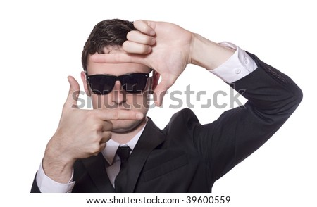 businessman in a black suit and sunglasses framing his face - stock photo