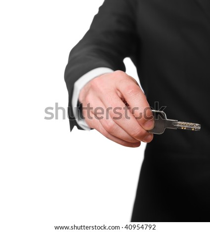 businessman in a black suit holding a key, isolated on white