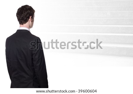 businessman in a black suit looking at stairs - stock photo