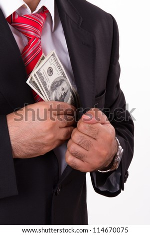 Businessman in a black suit putting hundred dollars in his pocket. - stock photo