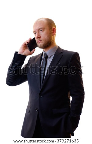 Businessman in a black suit, shirt and tie using a mobile phone in order to keep abreast of all the news. Makes the photo on the mobile phone, writes notes or new contacts and plays the game.