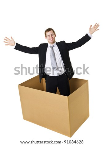 Businessman in a cardboard box isolated on white background - stock photo