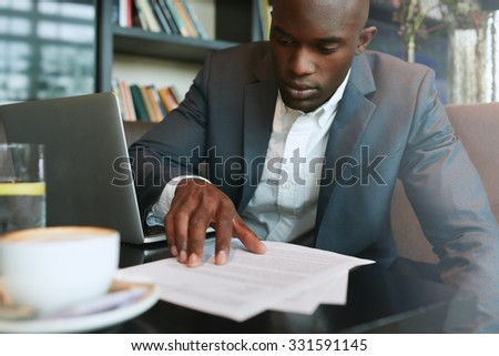 Businessman in a coffee shop reading a contract document. African business executive sitting at cafe working. - stock photo