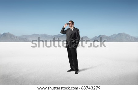 Businessman in a desert using binoculars