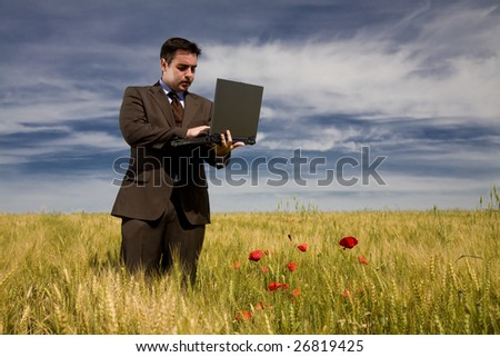 Businessman in a field working with his laptop - stock photo