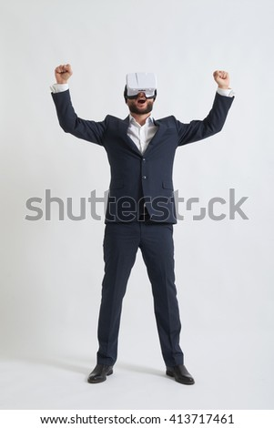 Businessman in a formal wear and virtual reality glasses feels joyful in 3d reality