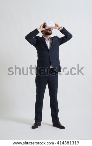 Businessman in a formal wear is watching something using virtual reality glasses