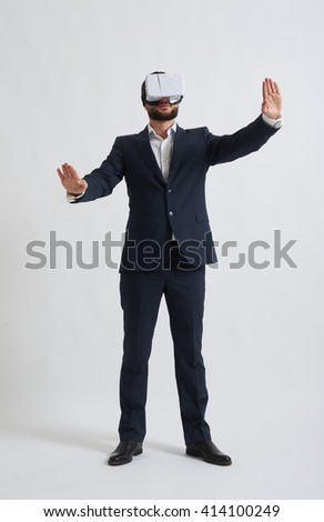 Businessman in a formal wear trying to push something wearing virtual reality glasses - stock photo