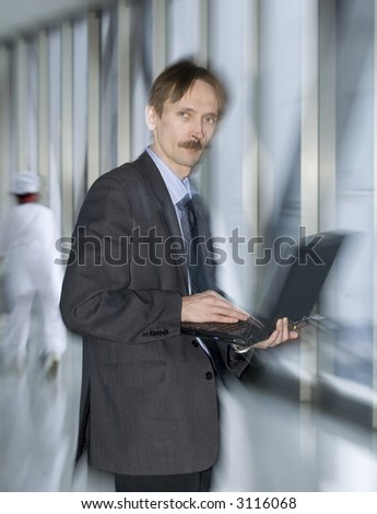 businessman in a hospital corridor with a motion blur