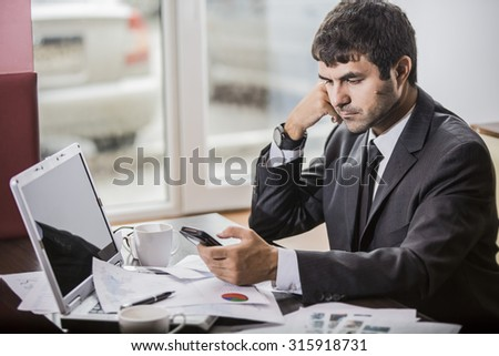 businessman in a jacketreading newspaper in smartphone in a coffee shop