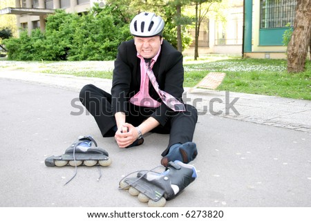Businessman in a lot of pain from roller blading - stock photo