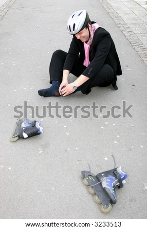 Businessman in a lot of pain from rollerblading - stock photo