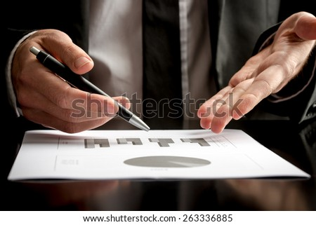 Businessman in a meeting or presentation holding a pen in one hand and pointing with the other to a document on the table in front of him, close up view. - stock photo