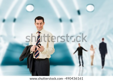 Businessman in a modern hall looking at his mobile phone and smiling with satisfaction