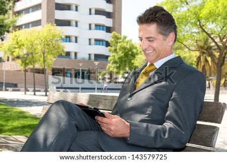 Businessman in a park bench with tablet