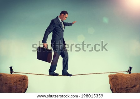 businessman in a predicament balancing on a tightrope  - stock photo