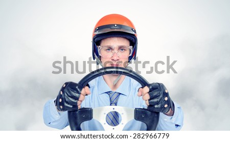 Businessman in a red helmet with steering wheel, car drive concept - stock photo