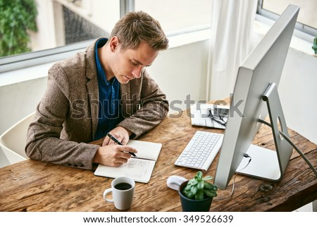 Businessman in a stylish jacket thinking deeply and writing notes in his journal while sitting at a neat and bright office space - stock photo