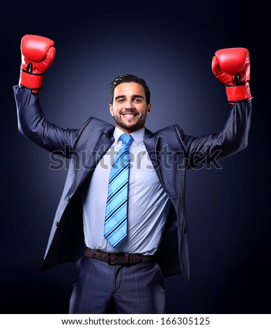 Businessman in a suit and boxing gloves, celebrating a win, isolated on black background - stock photo
