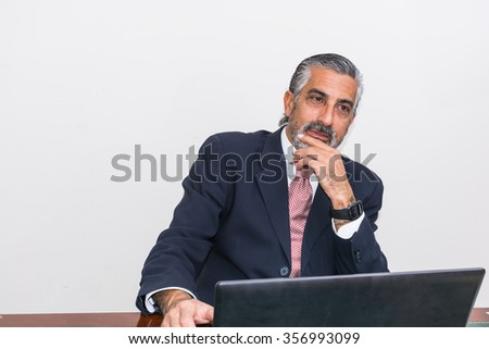 Businessman in a suit and tie, in his studio. At the desk, using pc.