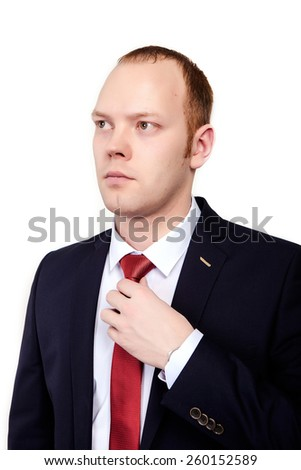Businessman in a suit corrects red tie on an isolated white background. - stock photo