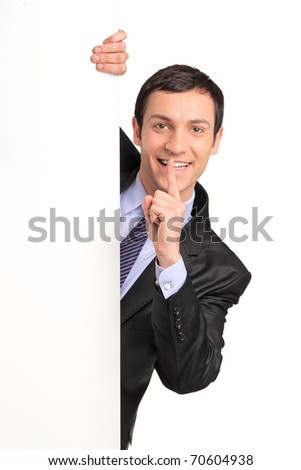Businessman in a suit gesturing silence with his finger over his mouth, behind white panel, isolated on white background - stock photo