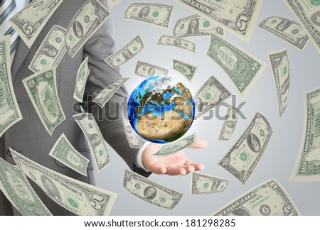 Businessman in a suit holding a earth. Money falling around. Elements of this image furnished by NASA