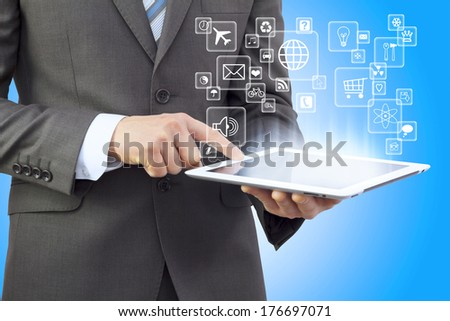 Businessman in a suit holding a tablet computer. Application icons are emitted from the tablet