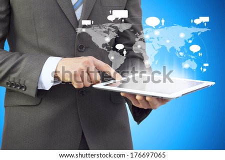 Businessman in a suit holding a tablet computer. The screen tablet - contacts and world map - stock photo