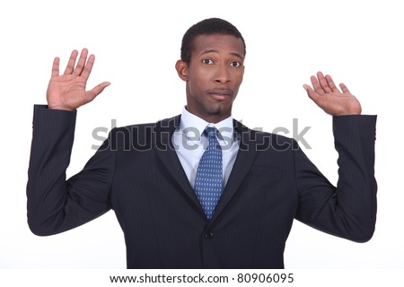 Businessman in a suit holding his hands in the air - stock photo