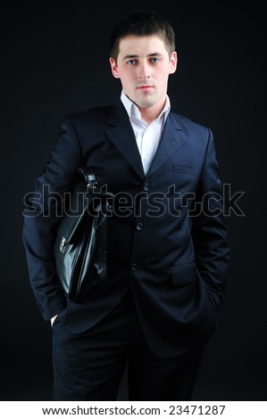 Businessman in a suit holds a briefcase - stock photo