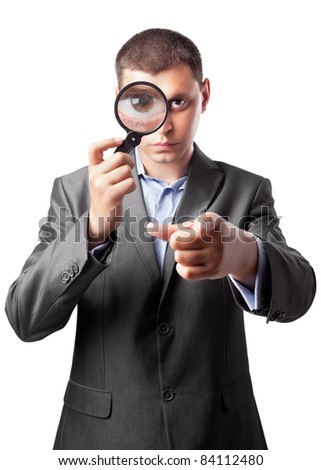 businessman in a suit looking through a magnifying glass isolated on white background - stock photo