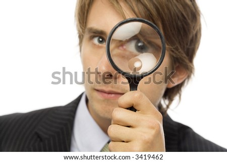 Businessman in a suit looks through a magnifying glass