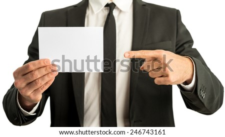 Businessman in a suit pointing to a blank white rectangular card that he is holding in his other hand ready for your text, closeup view of his hands and chest. - stock photo