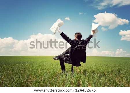 businessman in a suit sitting on a chair in a field and holding documents - stock photo