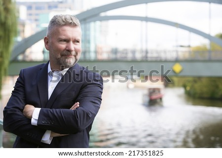 businessman in a suit standing in front of a bridge - stock photo