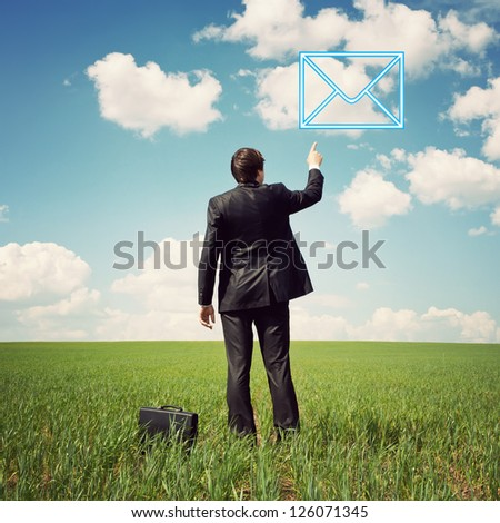 businessman in a suit standing in the field and points a finger at mail - stock photo