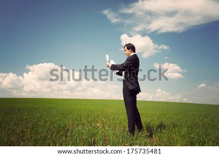 businessman in a suit standing on a green field with a blue sky and reads the newspaper or documents - stock photo