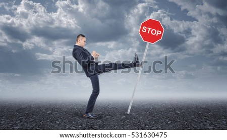 Businessman in a suit standing on the asphalt road and kicking the stop road sing. Business development. Moving forward. Aggressive marketing strategies.