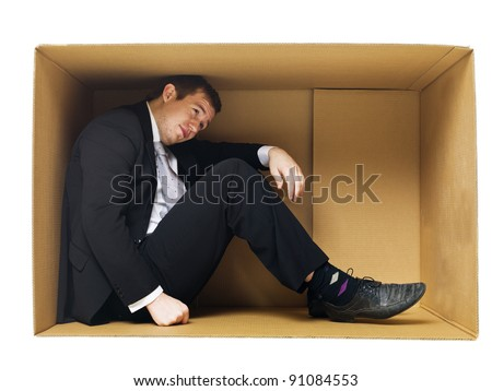 Businessman in a tight cardboard box isolated on white background - stock photo