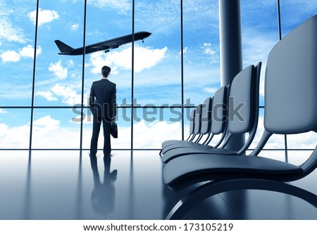 businessman in airport looking at airplane in sky