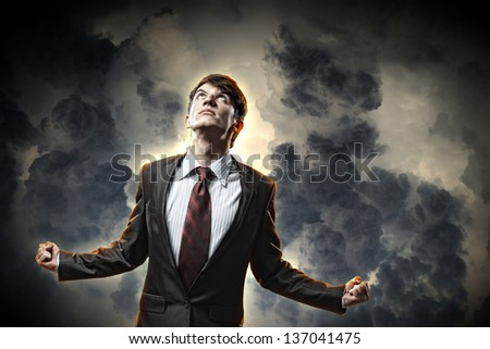 businessman in anger with fists clenched looking in the sky - stock photo