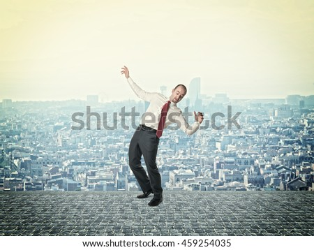 businessman in balance pose urban town background - stock photo