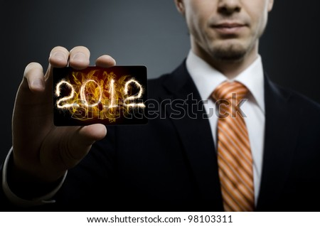 businessman in black costume and orange necktie reach out on camera and show credit card or visiting card, close up - stock photo