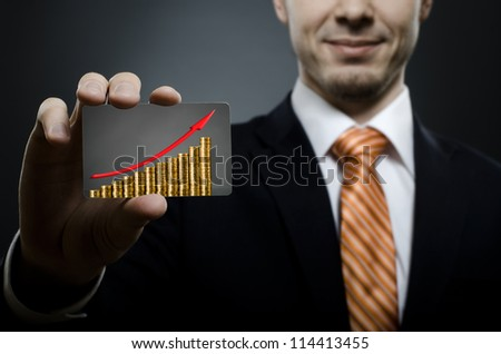 businessman in black costume and orange necktie reach out on camera and show credit card  with gold coins and red arrow up, close up - stock photo