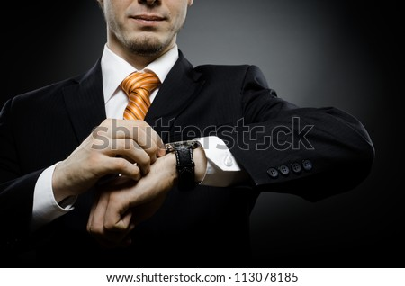 businessman in black costume wind clock (wristwatch) on hand - stock photo