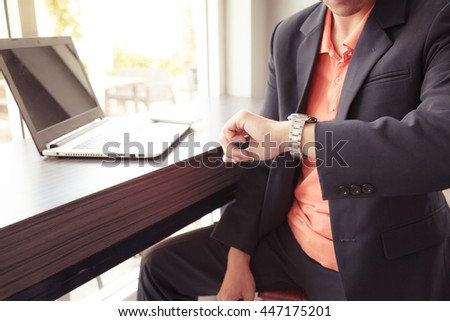 businessman in black costume wind clock (wristwatch) on hand, close up - stock photo